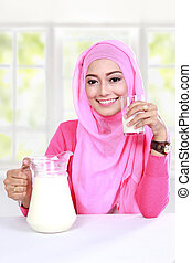 young muslim woman have a breakfast with milk