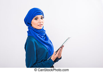Portrait of beautiful young muslim woman with file folder on a white background.