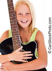beautiful young preteen girl holding a guitar