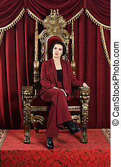 Portrait of beautiful young queen sitting on chair