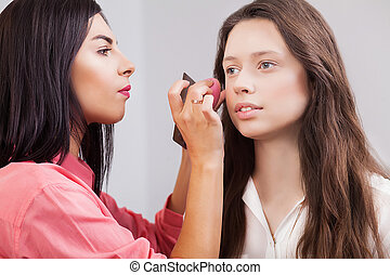 Portrait of beautiful young redheaded woman with esthetician making makeup eye shadow