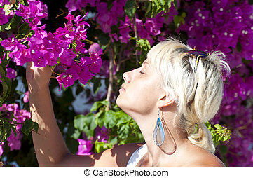 Portrait of beautiful young short-haired woman smelling pink flowers