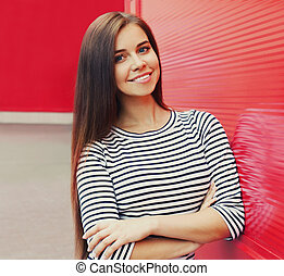 Portrait of beautiful young smiling brunette woman in a city