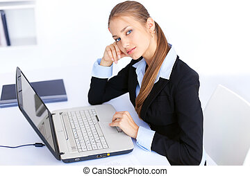 Portrait of beautiful young smiling business woman working on a laptop in office