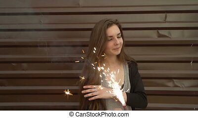 Portrait of beautiful young smiling girl on the background of the metal wall, holding sparkler in her hands and looking very happy, slow motion shot