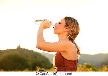beautiful young sports woman drinking water outside