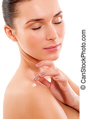 Portrait of Beautiful young woman applying cosmetics to her skin