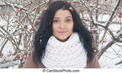 portrait of beautiful young woman at winter snowy day outdoors at viburnum background
