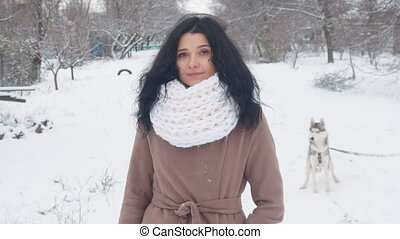 portrait of beautiful young woman at winter snowy day outdoors