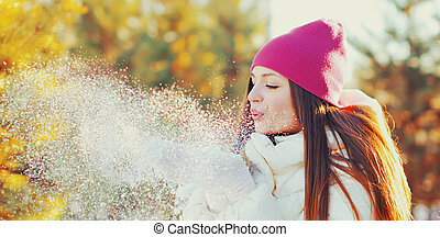 Portrait of beautiful young woman blowing snowflakes in winter over snowy background