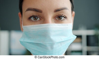 Portrait of beautiful young woman doctor wearing face mask indoors in office