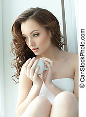 Portrait of beautiful young woman drinks coffee