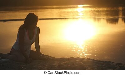 Portrait of beautiful young woman resting on the river bank. Slow motion