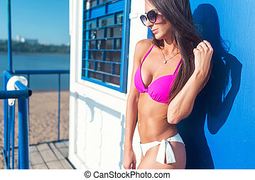 Portrait of beautiful young woman in bikini on beach posing.
