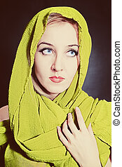 Portrait of beautiful young woman in bright, green head scarf on black background