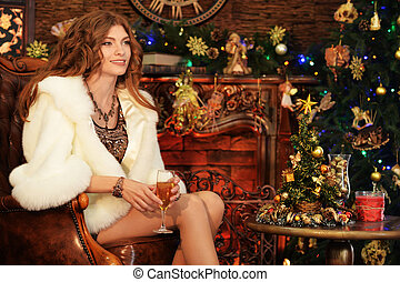 Portrait of beautiful young woman in fur coat sitting