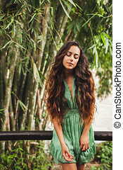 Portrait of beautiful young woman in green dress