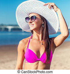 Portrait of beautiful young woman in hat posing in bikini on the beach