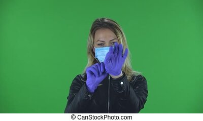Portrait of beautiful young woman in medical mask is looking at camera and puts on rubber gloves. Blonde with loose hair in a black jacket and jeans on a green screen in the studio. Health Protection Corona Virus Concept