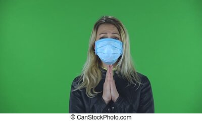Portrait of beautiful young woman in medical mask is looking straight and prays clasped hands palm to palm. Blonde with loose hair in a black jacket and jeans on a green screen in the studio. Health Protection Corona Virus Concept.