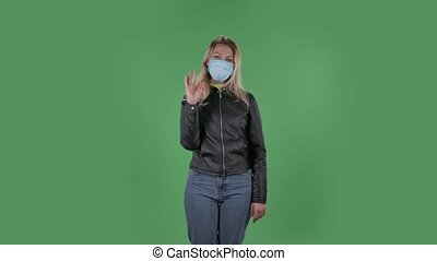 Portrait of beautiful young woman in medical mask is looking straight sighs relieved and making sign ok. Blonde with loose hair in a black jacket and jeans on a green screen in the studio. Health Protection Corona Virus Concept