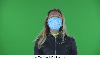 Portrait of beautiful young woman in medical mask is upset and tired looking straight. Blonde with loose hair in a black jacket and jeans on a green screen in the studio. Health Protection Corona Virus Concept
