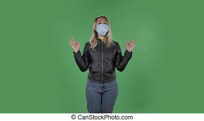 Portrait of beautiful young woman in medical protective face mask is looking at camera is relaxing and meditating. Blonde with loose hair in a black jacket and jeans on a green screen in the studio. Health Protection Corona Virus Concept