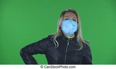 Portrait of beautiful young woman in medical protective face mask looking at camera and applying antiseptic on her hands in order to prevent the spread of coronavirus. Blonde with loose hair in a black jacket and jeans on a green screen in the studio. Health Protection Corona Virus Concept.