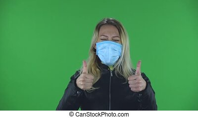 Portrait of beautiful young woman in medical protective face mask looking at camera and showing thumbs up gesture with both hands. Blonde with loose hair in a black jacket and jeans on a green screen in the studio. Health Protection Corona Virus Concept
