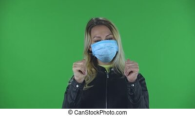 Portrait of beautiful young woman in medical protective face mask looking at camera and showing thumbs up and making sign ok with both hands. Blonde with loose hair in a black jacket and jeans on a green screen in the studio. Health Protection Corona Virus Concept