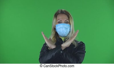 Portrait of beautiful young woman in medical protective face mask looking at camera and strictly gesticulates with hands crossed making X shape meaning denial saying NO and STOP. Blonde with loose hair in a black jacket and jeans on a green screen in the studio. Health Protection Corona Virus ...