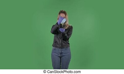 Portrait of beautiful young woman in medical protective face mask pours medicine from hand to hand in order to prevent the spread of coronavirus. Blonde with loose hair in a black jacket and jeans on a green screen in the studio. Health Protection Corona Virus Concept.