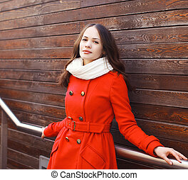 Portrait of beautiful young woman in red jacket on against a wooden wall