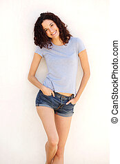 beautiful young woman in shorts smiling against white background