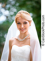 portrait of beautiful young woman in white dress walking in park