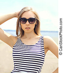 Portrait of beautiful young woman in sunglasses and striped dress over sea