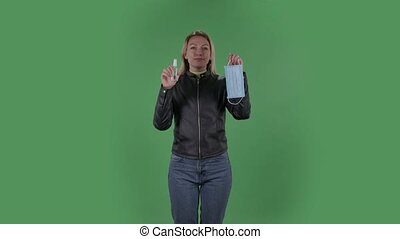 Portrait of beautiful young woman is looking straight and holding in hands a medical mask and an antiseptic. Blonde with loose hair in a black jacket and jeans on a green screen in the studio. Health Protection Corona Virus Concept