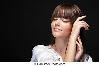 Portrait of beautiful young woman isolated on black background