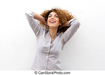 beautiful young woman laughing with hand in hair and looking up