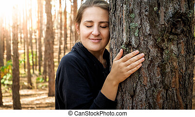 Portrait of beautiful young woman leaning and touching big old tree in forest. Concept of ecology, environment protection and harmony with nature