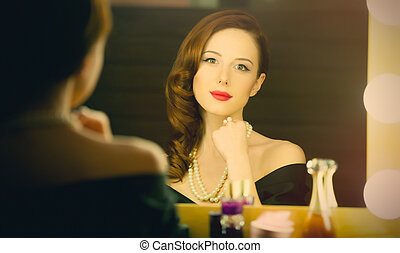 portrait of beautiful young woman looking at herself in the mirror and smiling