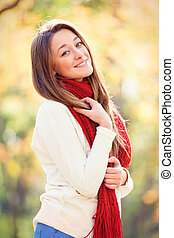 portrait of beautiful young woman on the wonderful autumn park background