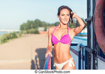 Portrait of beautiful young woman posing in bikini on the beach.