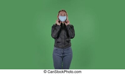 Portrait of beautiful young woman puts on medical mask. Blonde with loose hair in a black jacket and jeans on a green screen in the studio. Health Protection Corona Virus Concept.