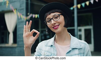 Portrait of beautiful young woman showing OK hand gesture...