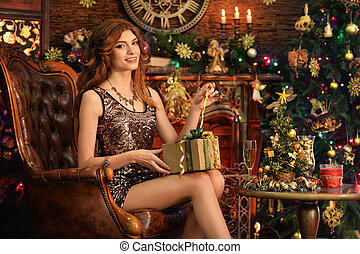 Portrait of beautiful young woman sitting in room decorated to Christmas