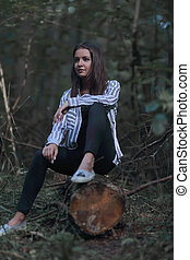 beautiful young woman sitting on a log