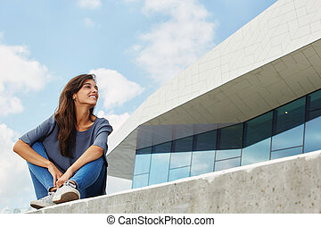 beautiful young woman sitting outside and looking away