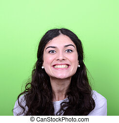 Portrait of beautiful young woman smiling against green background