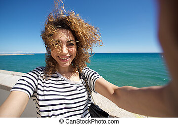 beautiful young woman smiling and taking selfie